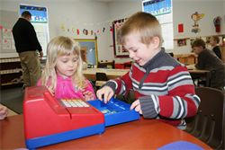 Two preschoolers playing with a cash register